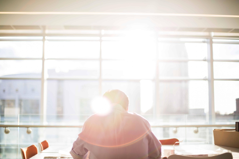 Een man werkend aan de employee experience scan in de zon achter een raam
